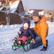 Young dad sledding his little adorable daughter on sunny winter day — Stok Fotoğraf #41244049