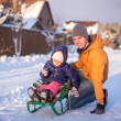 Stockfoto: Young dad sledding his little adorable daughter on sunny winter day