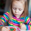 Little cute girl painting with pencils while sitting at her table — Stock Photo #41244105