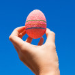 Stock Photo: Bright Beautiful pink Easter egg in hand on background of blue sky