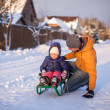 Stock Photo: Young dad sledding his little adorable daughter on sunny winter day