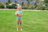 Little adorable girl playing with water gun outdoor in sunny summer day — Stockfoto