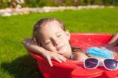 Portrait of relaxing adorable little girl enjoying her vacation in small pool outdoor — Stock Photo