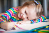 Little cute girl painting with pencils while sitting at her table — Stock Photo