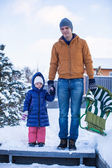 Young dad and little girl go sledding in a cold winter day — Stockfoto