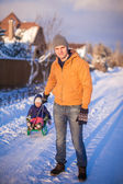 Young dad and little girl go sledding in a cold winter day — Stock Photo