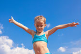 Adorable little girl spread her arms background of the blue sky — Stock Photo