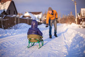 Young father sledding his little daughter on a sled in the snow outdoors — Stock Photo
