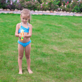 Little adorable girl playing with water gun outdoor in sunny summer day — Stock Photo
