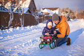 Young dad sledding his little adorable daughter on a sunny winter day — Stockfoto