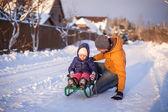 Jovem pai sua adorável filha de trenó em um dia ensolarado de inverno — Fotografia Stock