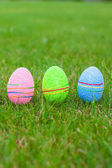 Multi-colored Easter eggs on green grass — Stock Photo