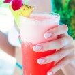 Tropical red cocktail in hand of a young woman on an exotic resort — Stock Photo #42374019