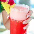 Tropical red cocktail in hand of a young woman on an exotic resort — Stock Photo #42374035