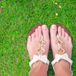 Closeup of bright flip flops and legs on green grass — Stock Photo #42374661