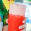 Tropical red cocktail in hand of a young woman on an exotic resort — Stock Photo #42375723