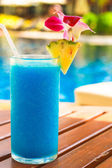 Tropical blue cocktail on a beach near swimming pool — Stock Photo