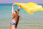 Beautiful young girl holding yellow fabric at wind in beach vacation — Stockfoto