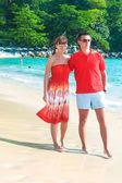 Güneşli bir günde egzotik kumsalda yürüyen genç romantik çift — Stok fotoğraf