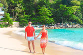 Young romantic couple walking on exotic beach in sunny day — Stock Photo