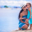 Little girl kissing her mother on a white, tropical beach — Stock Photo