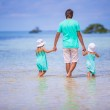 Back view of adorable little girls and young father walking at exotic island — Stock Photo #42821851
