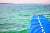 Small blue boat in open sea on desert island — Foto Stock