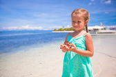 Little adorable girl with starfish in her hands at the tropical beach — Stock Photo