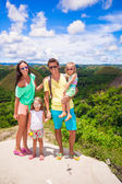 Young family of four on a background the Chocolate Hills in Bohol — Stock Photo