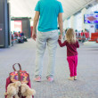 Rear view of little girl and young dad in the airport waiting for a flight — Stock Photo #43390637