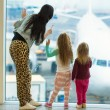 Little cute girls with mom near large window in airport looking at big aircraft — Stock Photo #43390643