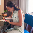 Young woman writing a letter at the table — Stockfoto