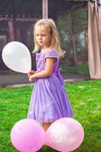 Little elegant girl on holiday with balloons — Stock Photo