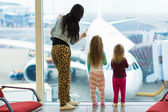 Little girls with their young mother at the large window in airport — Stock Photo