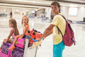 Young father and little cute daughters with luggage in airport — Stock Photo