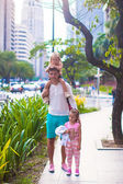 Young father walking with little girls in a big city outdoor — Stock Photo