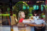 Adorable little girl in a beautiful cafe outside the window — Stock Photo
