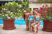 Little happy girls and young mother have fun near open-air pool — Stock Photo