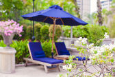 Two blue loungers with umbrellas near swimming pool in luxury hotel — Stock Photo