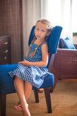 Retrato de niña adorable en silla en una habitación de hotel — Foto de Stock
