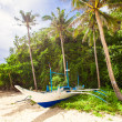 Filipino boat between high palms on white beach — Stock Photo