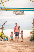 Little girls and young dad walking on a tropical beach — Stock Photo