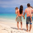 Back view of young beautiful family with two kids on tropical vacation — Stock Photo