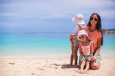 Young mother and her cute daughters have fun on exotic beach — Zdjęcie stockowe