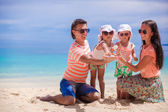 Young beautiful family of four enjoyed relaxing on the beach — Stock Photo