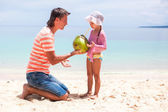 Portrait of cute little girl and young father with coconut milk on exotic beach — Stockfoto