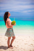 Young beautiful woman with a big coconut in hands at sunny hot day — Stock Photo