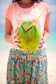 Closeup green big coconut in hands of young woman — Stock Photo