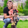 Young happy father and little cute girl with her puppy outside — Stock Photo #43861539