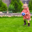 Little cute girl playing ball in the yard — Stock Photo #43861575